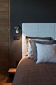 Multiple scatter cushions on bed with headboard upholstered in white against dark grey bedroom wall with sconce lamp