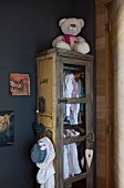 Girl's clothing hung in vintage cupboard and white teddy bear in corner of grey-painted room