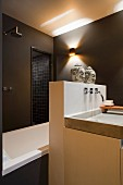 Designer washstand against masonry partition with two heads of Buddha on top screening bathtub and shower area in dark brown bathroom