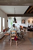 Cantilever and retro swivel chairs at long dining table below industrial-style pendant lamps in open-plan, loft-apartment interior