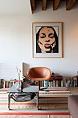 Coffee table with metal frame in front of pale brown, retro leather easy chair on brightly striped rug and modern portrait of woman on wall