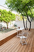 Simple garden chair and table on wooden terrace with integrated bench in courtyard with climber-covered wall
