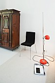 Retro standard lamp with red, spherical lampshade and black chair next to antique cupboard against white wall