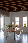 Dining set with classic chairs around table, house plants and vase of tulips in renovated loft apartment