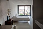 View from ensuite bathroom into minimalist bedroom with double bed and French windows leading to balcony