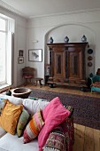 Colourful scatter cushions on sofa and antique cabinet in front of arched niche in traditional interior