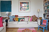 Pale sofa with colourful scatter cushions, blue chair with multi-coloured, striped upholstery and bookcase in corner of living room