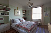 Double bed with ethnic bedspread in rustic bedroom