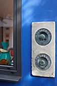 Concrete doorbell panel with vintage doorbells on azure-blue wall