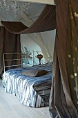 Double bed below wooden structure with casually draped canopy in attic bedroom