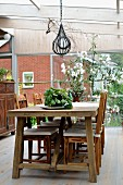 Rustic dining area in conservatory, potted herbs on wooden table below pendant lamp and white oleander bush against glass wall