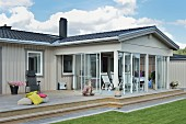 Pale grey wooden bungalow with glazed veranda and lawn in foreground