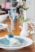 White linen napkin with napkin ring on place setting with rose in white china vase