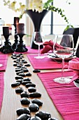 Festlich gedeckter Tisch mit pinkfarbenem Tischset und schwarzen, glänzenden Steinen