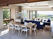 Solid wooden table, white plastic chairs, blue sofas and view of countryside through open folding terrace doors