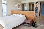 Electric guitar next to bedside table, double bed against half-height partition with desk in front of ensuite bathroom