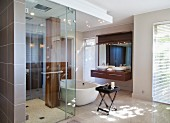 Rainfall shower and wooden column with row of shower nozzles in luxury shower in front of free-standing bathtub and exotic wood washstand