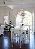 White dining table, refurbished second-hand chairs and Ghost chair below chandelier; bicycle in background in front of open arched terrace doors