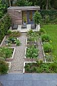 Geometrisch angelegte Hochbeete auf gekiestem Platz, im Hintergrund Terrasse mit modernen Outdoor-Möbeln und Gartenhäuschen
