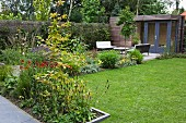 Beds of flowering plants in garden with seating area on terrace and summer house
