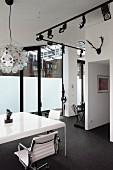 Weisser Tisch mit eleganten Bürostühlen und schwarzes Licht-Schienensystem mit Strahlern in Loftwohnung