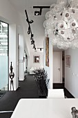 Designer pendant lamp above table in front of objets d'art in narrow hallway