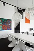 White dining set with classic shell chairs around modern table below spherical, white mesh designer lamps by Moooi