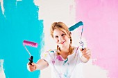 Young woman with hair in plaits holding up two pink and blue paint rollers