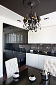 Chandelier hanging from ceiling panel in elegant kitchen-dining room with button-tufted chairs and white and glossy black cupboard fronts