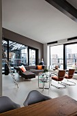 Loft apartment - view across dining area into lounge area with modern corner sofa and retro cantilever chairs in front of floor-to-ceiling windows