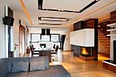 Blick über graue Couch in loftartigen Wohnraum, Essplatz gegenüber Raumteiler mit Kamin, in abgehängter Decke Einbaustrahler