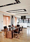 Elegant dining area with long wooden table and retro chairs in front of kitchen area in open-plan interior with recessed spotlights in ceiling panels