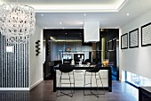 Black bar stools at counter in open-plan kitchen in modern interior with indirect ceiling lighting and chandelier to one side