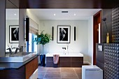 Elegant designer bathroom with brown-tiled wall and ceiling, washstand to one side and bathtub with tiled surround