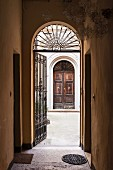 Entrance to Palazzo with wrought iron gate and view of front door of house opposite