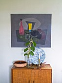 Blätterzweig in Vase und Kerzenhalter auf halbhohem Schrank aus Holz, an Wand aufgehängtes Bild