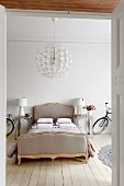 Double bed flanked by designer lamps on bedside cabinets and bicycles