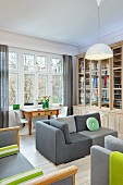 Elegant library with grey sofas, table with drawers and white Panton chairs in comfortable period interior