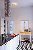 Minimalist, black and white kitchen with chequered floor and modern extractor hood