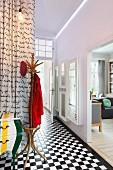 Altbau-Flurbereich mit Schachbrettmuster-Fliesenboden, Garderobenständer und Blick in Wohnbereich