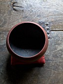 Rusty red ceramic bowl with black inside on rustic wooden surface