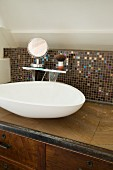Amorphous basin on custom, wood-veneer washstand with mosaic-tiled splashback and shaving equipment on shelf