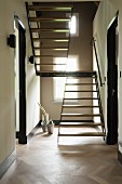 Custom, wood and metal staircase in narrow hallway with herringbone parquet floor