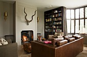 Brown leather sofa and armchair in front of fire in open fireplace below hunting trophy in elegant interior