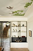 Exhibition pieces on custom shelving in elegant interior with ceiling mural