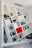 Slanting bookcase built onto wall and shell chair