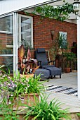 Potted plants on terrace, sliding door with view of armchair and matching footstool against brick wall