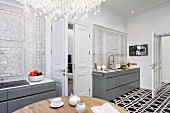 Dining table, modern kitchen counters in niches, ornamental pattern on wall and tiled floor with black and white, geometric pattern
