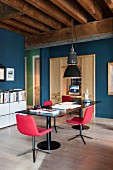 Steel table, red retro chairs and old industrial lamp as dining area and home office in open-plan, loft-apartment interior in old factory building