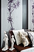 Wall hangings with Japanese bamboo drawings behind double bed with scatter cushions and Geisha figurines on bedside table